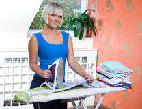 Attractive woman ironing. Clothes in her home Stock Images