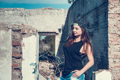 Attractive woman in jean and cup outfit posing in old ruined factory house. royalty free stock image