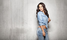 Attractive woman in jeans touching her hair. Attractive brunette woman in jeans touching her hair on gray background Royalty Free Stock Image