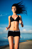 Attractive woman jogging on the beach Stock Images
