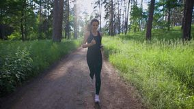 Attractive woman jogging on the trail in the park. Sport and recreation