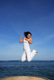 Attractive Woman Jumping. Attractive asian woman jumping on a beach Royalty Free Stock Photos