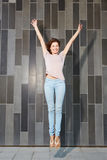 Attractive woman jumping in air with arms extended. Full length portrait of attractive woman jumping in air with arms raised Royalty Free Stock Photo