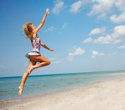 Attractive woman jumping on beach Stock Image