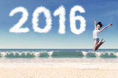 Attractive woman jumping at coast with numbers 2016. Image of beautiful young woman jumping and dancing on the beach with cloud shaped numbers 2016 Royalty Free Stock Photography