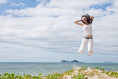 Attractive woman jumping of joy on tropical beach. A beautiful girl jumping and laughing on a sunny tropical beach Stock Photo