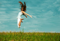 Attractive woman jumping in sky. Young attractive woman jumping in sky, against green of summer park Royalty Free Stock Photography