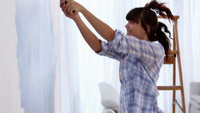 Attractive woman jumping to paint her wall Stock Photography