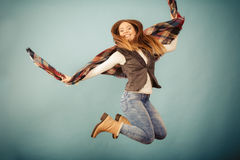 Attractive woman is jumping up. Movement fun and fashion concept. Attractive woman is jumping up. Beautiful girl with long hair wearing jeans and scarf Royalty Free Stock Photo