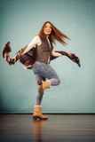 Attractive woman is jumping up. Movement fun and fashion concept. Attractive woman is jumping up. Beautiful girl with long hair wearing jeans and scarf Royalty Free Stock Images