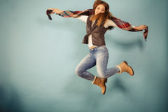 Attractive woman is jumping up. Movement fun and fashion concept. Attractive woman is jumping up. Beautiful girl with long hair wearing jeans and scarf Royalty Free Stock Image