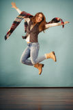 Attractive woman is jumping up. Movement fun and fashion concept. Attractive woman is jumping up. Beautiful girl with long hair wearing jeans and scarf Stock Images