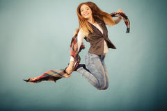 Attractive woman is jumping up. Movement fun and fashion concept. Attractive woman is jumping up. Beautiful girl with long hair wearing jeans and scarf Stock Image