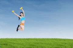 Attractive woman jumps with her dumbbells Stock Photos