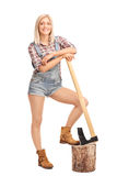 Attractive woman in jumpsuit leaning on an axe Stock Photography