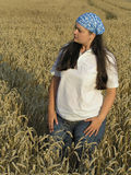 Attractive woman with kerchief. Girl standing in the field stock photo