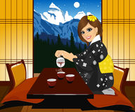 Attractive woman in kimono pouring tea. Interior of traditional japanese interior Kyoto Royalty Free Stock Photography