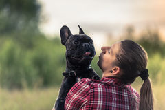 Attractive woman kissing French Bulldog puppy.  Royalty Free Stock Images