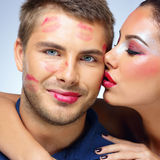 Attractive woman kissing happy man Stock Image