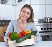 Attractive woman in the kitchen cooking with fresh vegetables Stock Image