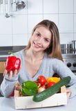 Attractive woman in the kitchen loves fresh vegetables Stock Photography