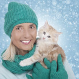 Attractive woman with kitten in front of winter background Royalty Free Stock Images