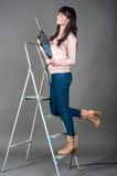 Attractive woman on ladder with heavy drill Royalty Free Stock Photo