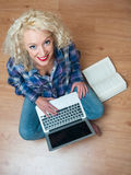 Attractive woman with laptop and book Stock Images