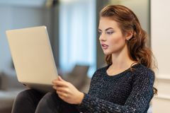 Attractive woman with laptop at home. Young woman working on computer while sitting at home. Enjoying time at home stock photography