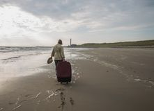 Attractive woman with a large suitcase walks along empty beach o. Woman with a large suitcase walks along the shore of the sea towards the horizon and lighthouse royalty free stock images