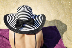 Attractive woman in a large summer hat and black bikini on the beach. Royalty Free Stock Photography