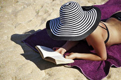 Attractive woman in a large summer hat and black bikini reading on the beach. Stock Photo