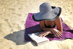 Attractive woman in a large summer hat and black bikini reading on the beach. Royalty Free Stock Photography