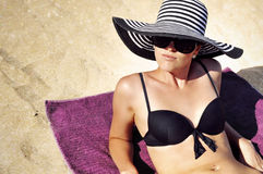 Attractive woman in a large summer hat, sunglasses and black bikini on the beach. Royalty Free Stock Image