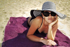 Attractive woman in a large summer hat, sunglasses and black bikini on the beach. Stock Images