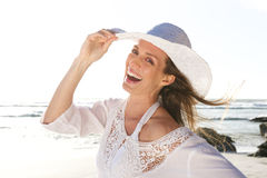 Attractive woman laughing with hat at the beach Royalty Free Stock Photos