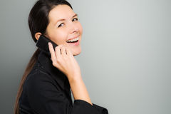 Attractive woman laughing on her mobile phone Stock Photography