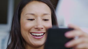 Attractive woman laughing on her phone in slow motion stock video footage