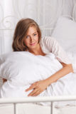 Attractive woman laying in the bed Royalty Free Stock Photos