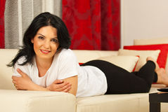 Attractive woman laying on sofa. Attractive woman laying and relaxing on sofa in her living room Royalty Free Stock Photo