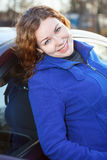 Attractive woman leaned to car smiling Royalty Free Stock Photos