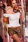 Attractive woman in leather pants with beer mug and pretzel Stock Images
