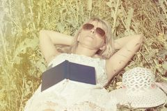 Attractive woman lies in the field and dreams after reading the book. Attractive woman lies in the field and dreams after reading the book royalty free stock image