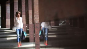 Attractive woman in light summer blouse and jeans after shopping walking near granite columns of modern city building. And talking on mobile phone stock footage