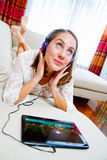 Attractive woman listen music on sofa Royalty Free Stock Photos