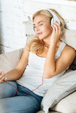 Attractive woman listening to music in bed Stock Photos