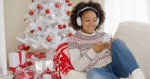 Attractive woman listening to music at Christmas Royalty Free Stock Image