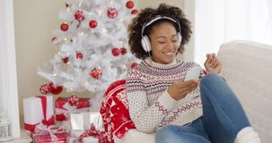Attractive woman listening to music at Christmas stock video