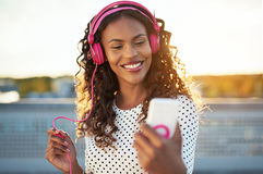 Attractive woman listening to music on her mobile. On a set of trendy pink headphones smiling happily as she checks the screen of her phone Royalty Free Stock Photos