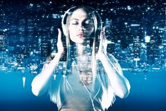 Attractive woman listening to music. Portrait of attractive young woman listening to music through headphones on abstract upside down night city background Stock Photos